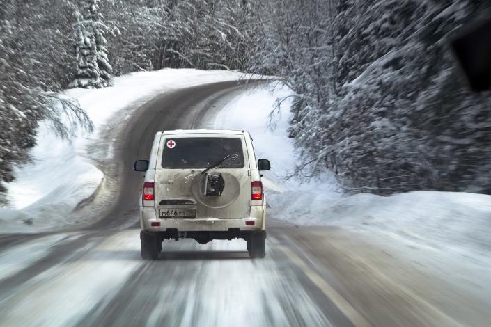 A medical car moves along a snowy road carrying COVID-19 vaccines heading to the village of Ikhala in Russia's Karelia region, Tuesday, Feb. 16, 2021. Russia's rollout of its coronavirus vaccine is only now picking up speed in some of its more remote regions, although experts say the campaign is still moving slowly. (AP Photo/Dmitri Lovetsky)