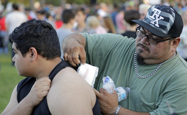 <p>Gabriel San Miguel, right, removes a bandage from his son's, Santa Fe High School student Abel San Miguel, back after attending a prayer vigil following a shooting at Santa Fe High School in Santa Fe, Texas, on Friday, May 18, 2018. San Miguel was inside a classroom when a gunman opened fire. (Photo: David J. Phillip/AP) </p>