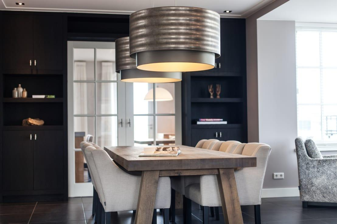 <p>The drama and design of this dining space has us beside ourselves with jealousy that this isn't our homes! A beautiful yet sturdy table meets surprisingly luxurious chairs with such harmony and then there's those overhead lights that bring everything together. Against the black wall in the background, the soft colours of this installation work so well.</p>  Credits: homify / Bob Romijnders Architectuur & Interieur