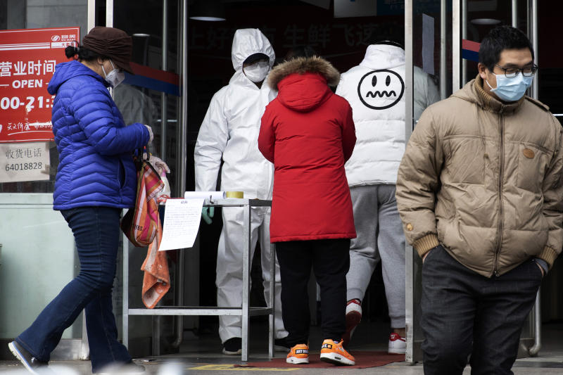 FILE - In this Thursday, Feb. 27, 2020, file photo, a worker in overalls screen for fever at the entrance to a supermarket in Beijing. Health officials reported the first U.S. drug shortage tied to the viral outbreak that is disrupting production in China, but they declined to identify the manufacturer or the product. The Food and Drug Administration said late Thursday, that the drug's maker contacted health officials recently about the shortage, which it blamed on a manufacturing issue with the medicine's key ingredient. (AP Photo/Ng Han Guan, File)