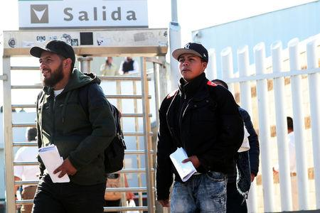 FILE PHOTO: Central American asylum seekers exit the Chaparral border crossing gate after being sent back to Mexico by the U.S. in Tijuana, Mexico