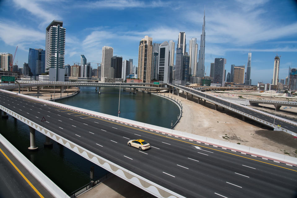 A lone taxi cab drives over a typically gridlocked highway with the Burj Khalifa, the world's tallest building, in the skyline behind it in Dubai, United Arab Emirates, Monday, April 6, 2020. Dubai, one of seven sheikdoms in the United Arab Emirates, is now under a 24-hour lockdown over the new coronavirus pandemic. (AP Photo/Jon Gambrell)