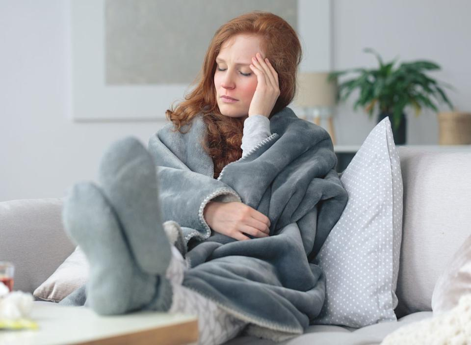 Sick woman sitting on couch wrapped in blanket