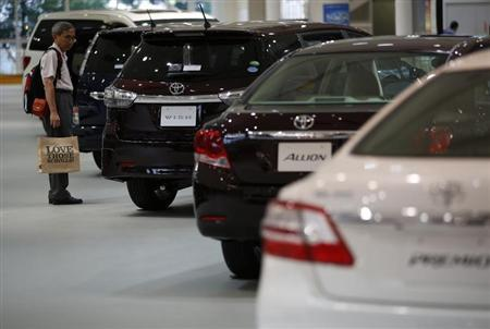 A visitor looks at Toyota Motor Corp's cars at the company's showroom in Tokyo August 1, 2013. REUTERS/Issei Kato