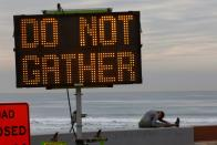 A woman stretches near a warning sign on the beach as new stay-at-home orders begin in Southern California