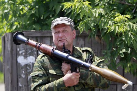 An armed pro-Russian separatist stands guard in Seversk (Siversk), located near the town of Krasny Liman, Donetsk region, June 19, 2014. REUTERS/Shamil Zhumatov