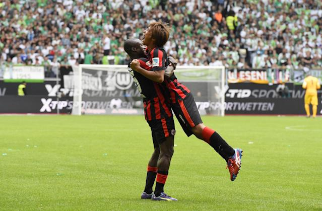 Frankfurt's Japanese midfielder Takashi Inui (R) is hugged by Ivorian defender Constant Djakpa after scoring during the German first division Bundesliga football match VfL Wolfsburg vs Eintracht Frankfurt in Wolfsburg on August 30, 2014 DFL RULES TO LIMIT THE ONLINE USAGE DURING MATCH TIME TO 15 PICTURES PER MATCH. IMAGE SEQUENCES TO SIMULATE VIDEO IS NOT ALLOWED AT ANY TIME. FOR FURTHER QUERIES PLEASE CONTACT DFL DIRECTLY AT + 49 69 650050. (AFP Photo/Tobias Schwarz)