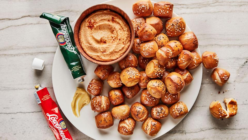 """These pretzel nubbins are crunchy on the outside and soft and chewy on the inside. Instead of using lye, which can be hard to find and work with, we achieved the deep mahogany color by boiling them in a baking soda bath. Make sure you serve them with our <a href=""""https://www.bonappetit.com/recipe/spicy-cheddar-cheese-spread?mbid=synd_yahoo_rss"""" rel=""""nofollow noopener"""" target=""""_blank"""" data-ylk=""""slk:Spicy Cheddar Cheese Spread"""" class=""""link rapid-noclick-resp"""">Spicy Cheddar Cheese Spread</a>; we also love this <a href=""""https://www.amazon.com/D%C3%BCsseldorfer-L%C3%B6wensenf-Scharf-Mustard-Original/dp/B004WW9NV4/"""" rel=""""nofollow noopener"""" target=""""_blank"""" data-ylk=""""slk:German mustard in a tube"""" class=""""link rapid-noclick-resp"""">German mustard in a tube</a>. <a href=""""https://www.bonappetit.com/recipe/pretzel-bites?mbid=synd_yahoo_rss"""" rel=""""nofollow noopener"""" target=""""_blank"""" data-ylk=""""slk:See recipe."""" class=""""link rapid-noclick-resp"""">See recipe.</a>"""