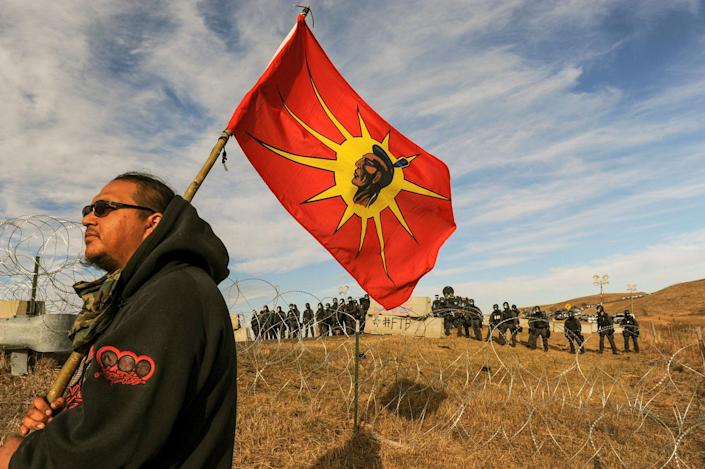<p>A protesters flies a flag during a stand off with police during a protest against the Dakota Access pipeline near the Standing Rock Indian Reservation near Cannon Ball, North Dakota November 6, 2016. (Photo: Stephanie Keith/Reuters) </p>