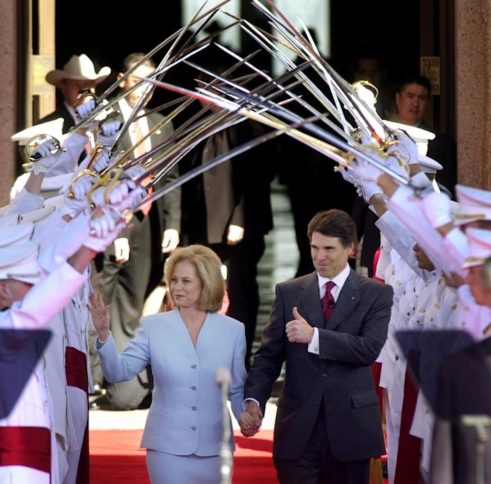 FILE - In this Jan. 21, 2003, file photo Texas Gov. Rick Perry, with his wife Anita, walks under the Ross Volunteers saber arch during Perry's inauguration in Austin, Texas. Perry announced Monday, July 8, 2013, that he would not seek re-election as Texas governor next year. (AP Photo/Eric Gay, File)