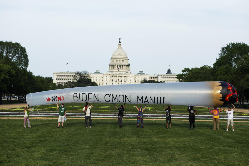 Members of the DC Marijuana Justice community hold a 51 blow-up joint on the National Mall ahead of President Joe Bidens address to a joint session of Congress to call on the administration to take action on legalization and expungement of criminal records on Wednesday, April 28, 2021. (Tom Williams/CQ-Roll Call, Inc via Getty Images)