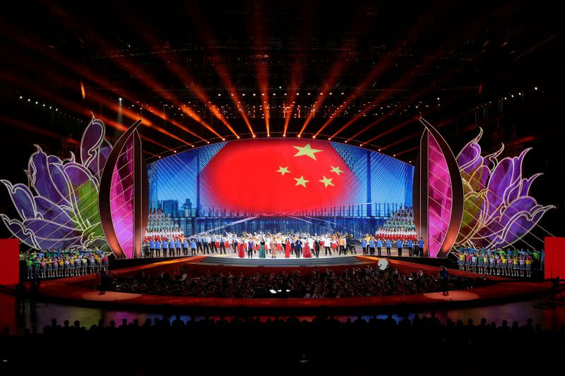 Performers take part in a cultural performance with an image of the Chinese flag seen in the background in Macau