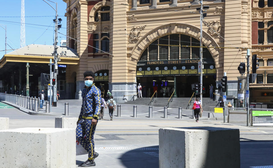 A man wearing a mask walks past Flinders Street Station in Melbourne, Australia, Wednesday, Oct. 28, 2020. In Melbourne, Australia's former coronavirus hot spot, restaurants, cafes and bars were allowed to open and outdoor contact sports can resume Wednesday, emerging from a lockdown due to the coronavirus outbreak. (AP Photo/Asanka Brendon Ratnayake)