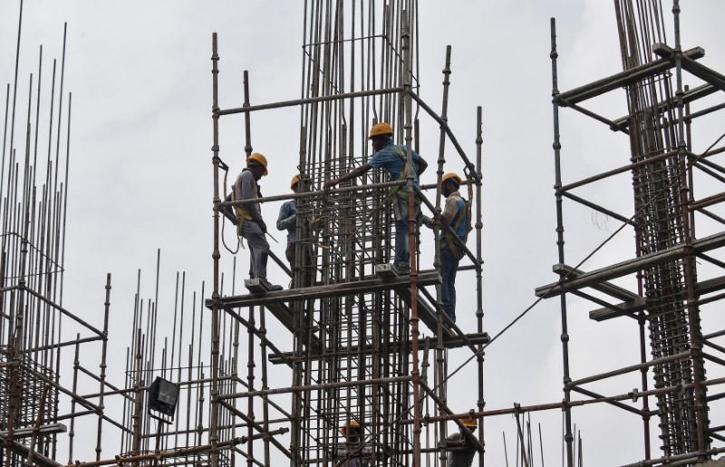 Workers erect scaffolding at a construction site of a metro rail station in Kolkata