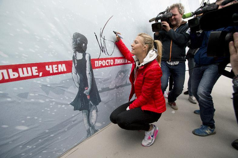 Russian tennis player Maria Sharapova signs her autograph on the wall at her first court in Riviera Park, Wednesday, Feb. 5, 2014, in Sochi, Russia, prior to the start of the 2014 Winter Olympics. (AP Photo/Pavel Golovkin)