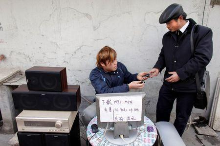 A man returns a cell phone to a customer after downloading music onto it at a street stand in Shanghai