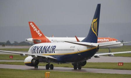 A Ryanair aircraft taxis behind an easyJet aircraft at Manchester Airport in Manchester