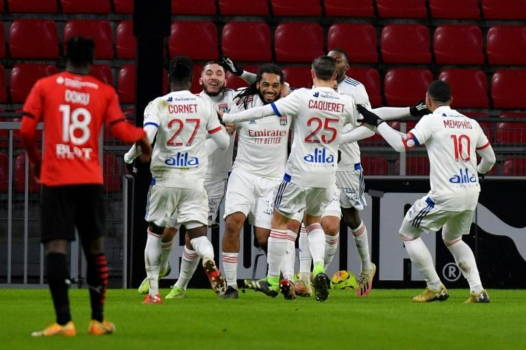 Lyon players celebrate Jason Denayer's late equaliser at Rennes that kept them on top of Ligue 1