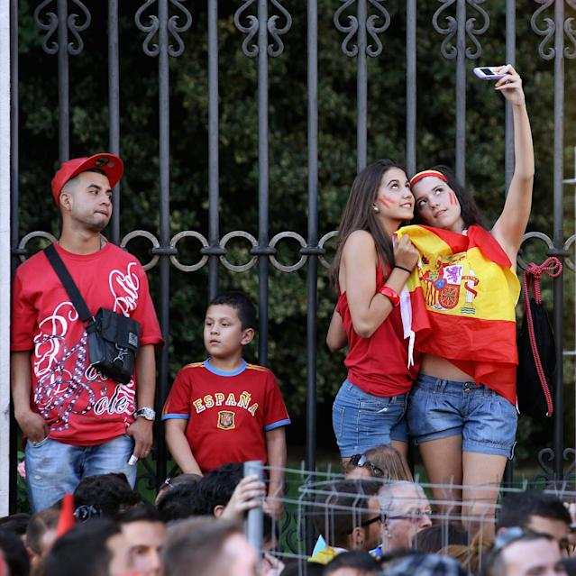 MADRID, SPAIN - JULY 02: Two Spain supporters take a photograph of themselves draped in the national flag as they prepare to congratulate their team's players on their return to Madrid following their victory in Euro 2012 football championships on July 2, 2012 in Madrid, Spain. Spain beat Italy 4-0 in the UEFA EURO 2012 final match in Kiev, Ukraine, on July 1, 2012. (Photo by Oli Scarff/Getty Images)
