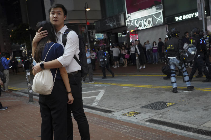 A couple react as policemen patrol at Causeway Bay in Hong Kong, Tuesday, Nov. 12, 2019. Police and protesters battled outside university campuses and several thousand demonstrators blocked roads as they took over a central business district at lunchtime on Tuesday in another day of protest in Hong Kong. (AP Photo/Vincent Yu)