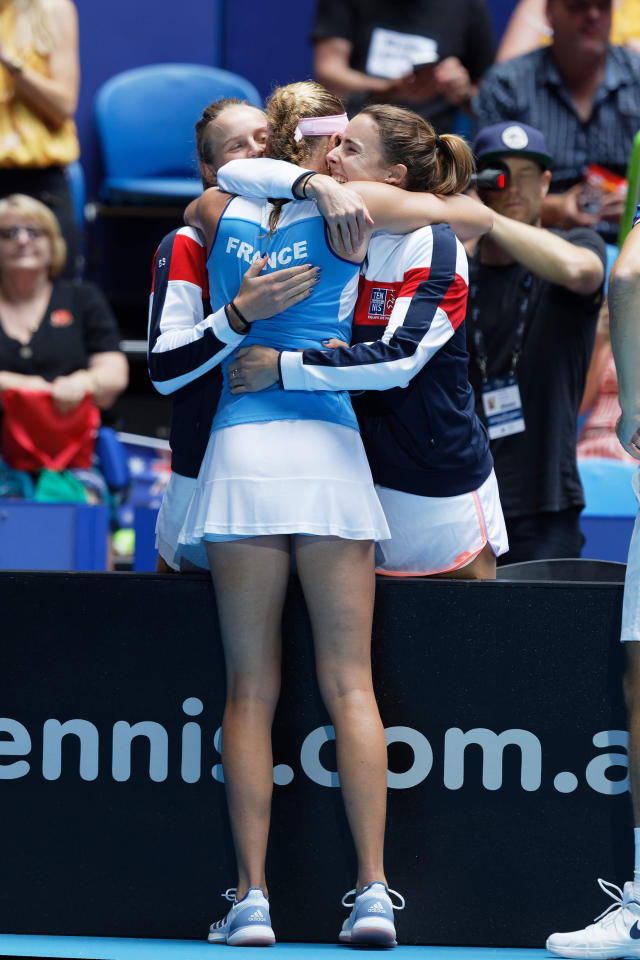 France's Kristina Mladenovic is hugged by teammates Alize Cornet, right, and Fiona Ferro after winning her match against Australia's Ash Barty during their Fed Cup tennis final in Perth, Australia, Sunday, Nov. 10, 2019. (AP Photo/Trevor Collens)