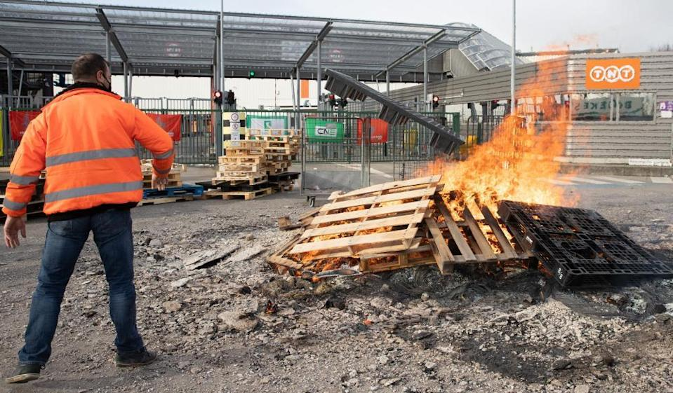 Workers build a protest fire at the entrance of the FedEx/TNT facility near Liège airport.