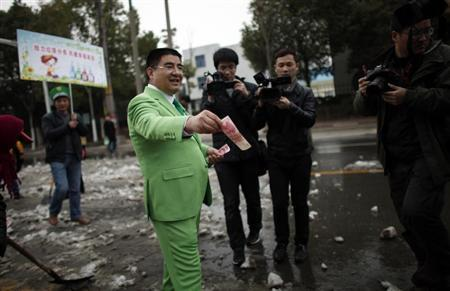 "Chinese multimillionaire Chen Guangbiao gives money away to street cleaners during an event organized by him, where people representing companies, which Chen claims pollute the environment, attend a parade to be publicly ""shamed"", in Nanjing, Jiangsu province February 21, 2013. REUTERS/Carlos Barria"