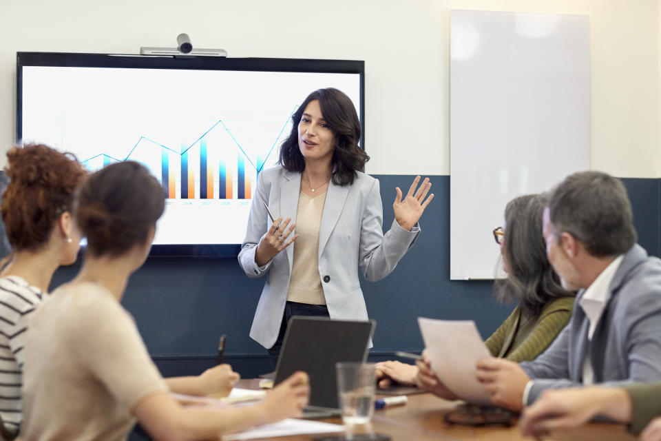 Confident businesswoman giving presentation to colleagues in board room. Entrepreneur is explaining development graph to partners. They are planning at creative office.