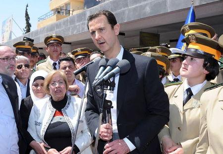 President Bashar al-Assad addresses his supporters at a school in an undisclosed location during an event to commemorate Syria's Martyrs' Day