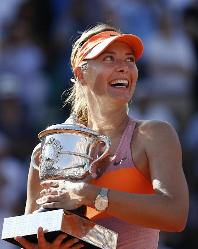 Russia's Maria Sharapova holds the trophy after winning the final of the French Open tennis tournament against Romania's Simona Halep at the Roland Garros stadium, in Paris, France, Saturday, June 7, 2014. Sharapova won in three sets 6-4, 6-7, 6-4. (AP Photo/Darko Vojinovic)