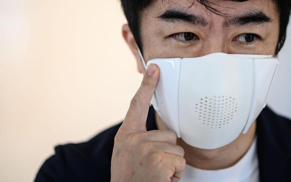 Donut Robotics chief executive Taisuke Ono poses for a photo wearing the company's smart face mask - Philip Fong/AFP