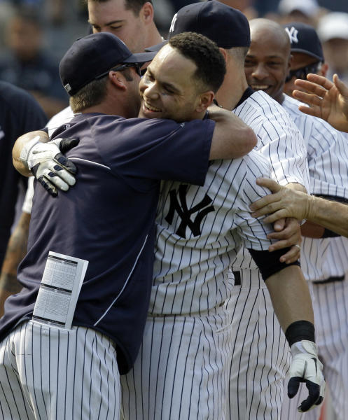 New York Yankees batting coach Kevin Long, left, embraces Yankees' Russell Martin after Martin's ninth-inning walk-off solo home run lifted them to a 5-4 victory over the New York Mets in a baseball game at Yankee Stadium in New York, Sunday, June 10, 2012. (AP Photo/Kathy Willens)