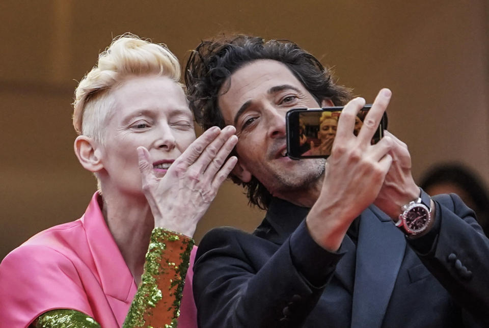 FILE - In this July 12, 2021 file photo Tilda Swinton, left, and Adrien Brody take a selfie photograph upon arrival at the premiere of the film 'The French Dispatch' at the 74th international film festival, Cannes, southern France. (AP Photo/Brynn Anderson, File)