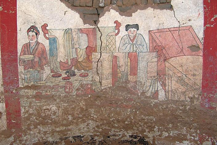 The murals on the west wall of the 1,000-year-old tomb depict articles of clothing as well as two servants. <cite>Courtesy of Chinese Cultural Relics</cite>