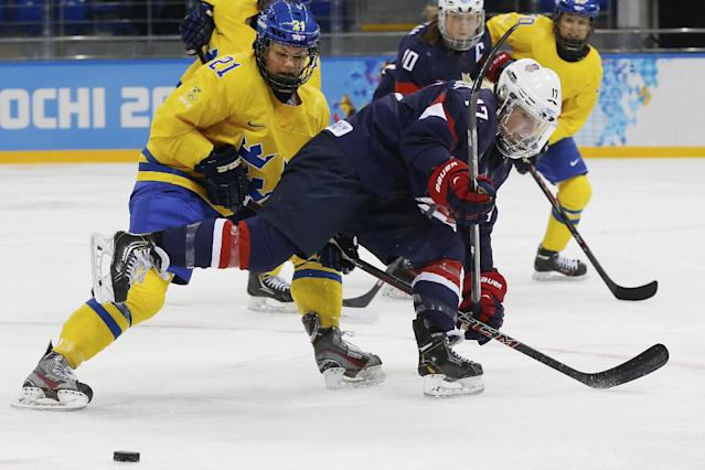 Jocelyne Lamoureux of the United States skates past the puck under pressure from Erica Uden Johansson of Sweden during the first period of the 2014 Winter Olympics women's semifinal ice hockey game at Shayba Arena Monday, Feb. 17, 2014, in Sochi, Russia. (AP Photo/Petr David Josek)