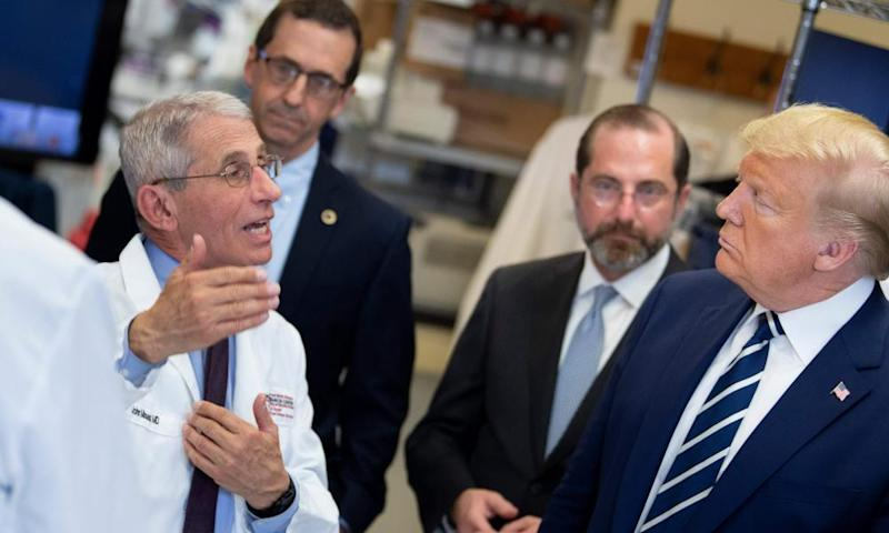 Dr Fauci speaks to US President Donald Trump during a tour of the National Institutes of Health's Vaccine Research Center