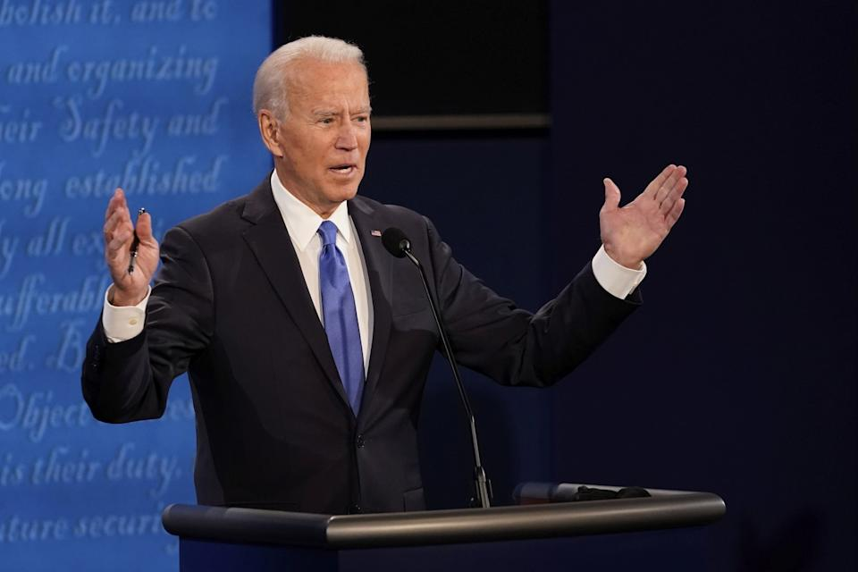 Joe Biden gestures with both hands as he speaks on stage