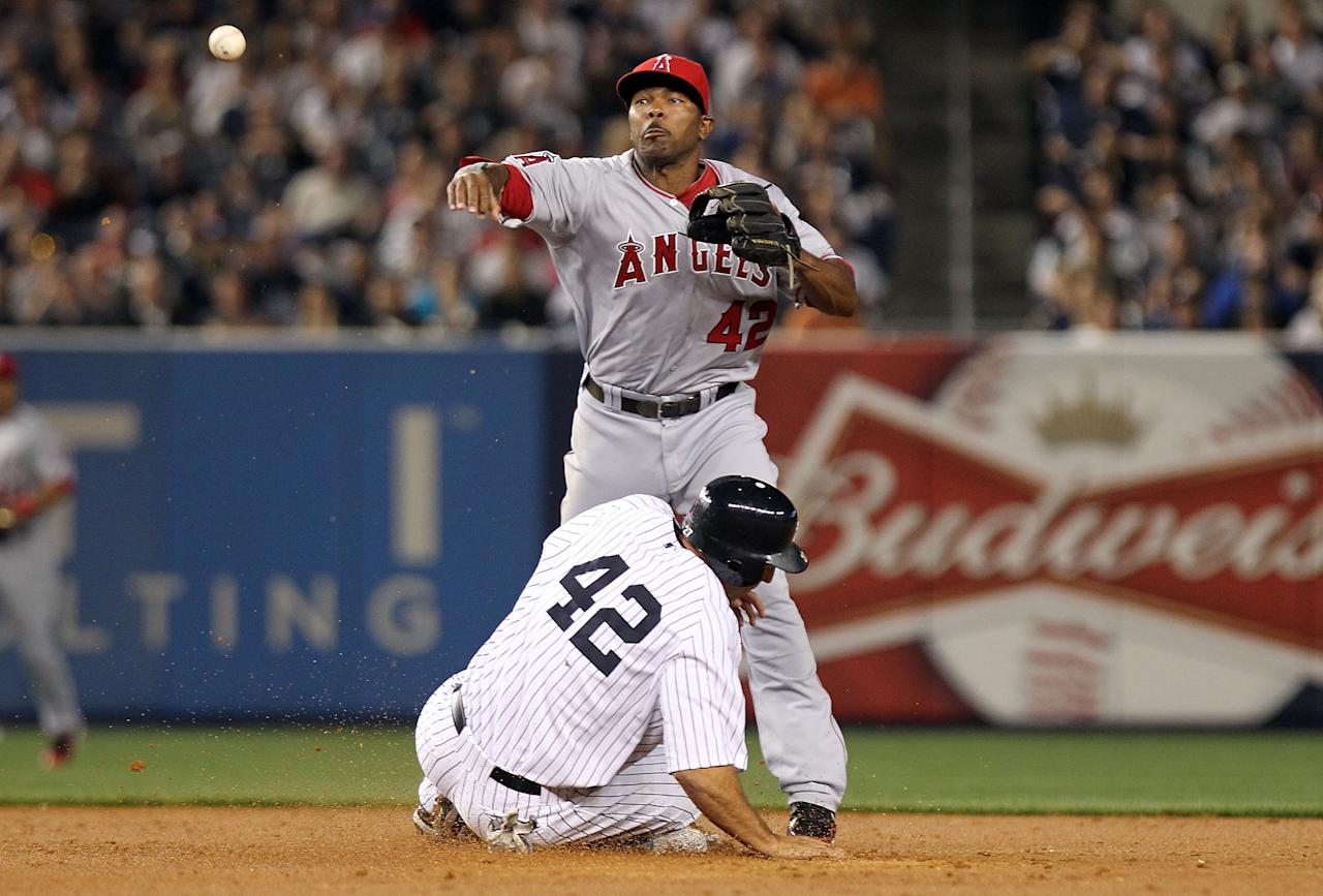 NEW YORK, NY - APRIL 15: Howie Kendrick of the Los Angeles Angels of Anaheim turns a double play over a sliding Raul Ibanez of the New York Yankees  at Yankee Stadium on April 15, 2012 in the Bronx borough of New York City. In honor of Jackie Robinson Day, all players across Major League Baseball will wear number 42.  (Photo by Nick Laham/Getty Images)