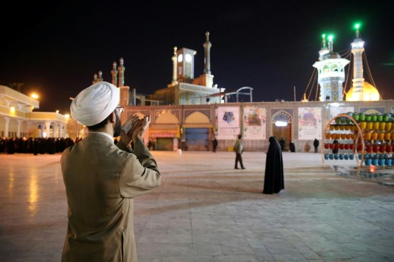 A cleric prays outside the Fatima Masumeh shrine in Iran's holy city of Qom
