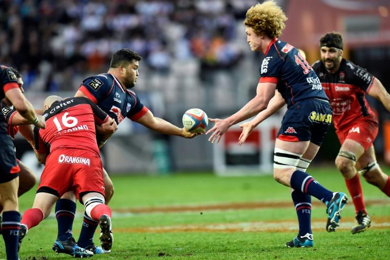 Grenoble's prop Ali Oz (L) passes the ball to lock Thomas Jolmes on March 19, 2016