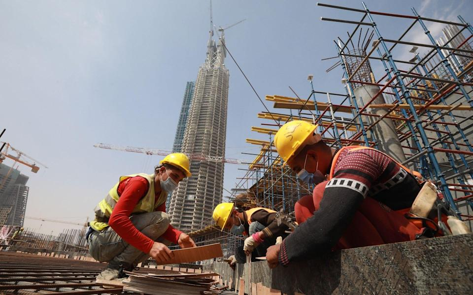 Egyptians laborers work at a construction site in the central business district of the new administrative capital, 45 kilometers east of Cairo - KHALED ELFIQI/EPA-EFE/Shutterstock