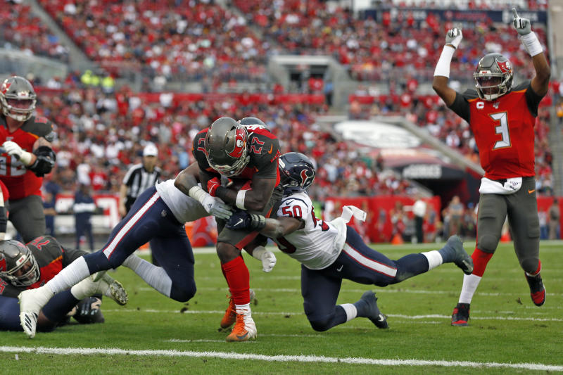 Tampa Bay Buccaneers running back Ronald Jones II (27) slips between Houston Texans inside linebacker Zach Cunningham (41) and linebacker Tyrell Adams (50) for a score during the first half of an NFL football game Saturday, Dec. 21, 2019, in Tampa, Fla. Quarterback Jameis Winston (3) celebrates the play. (AP Photo/Mark LoMoglio)