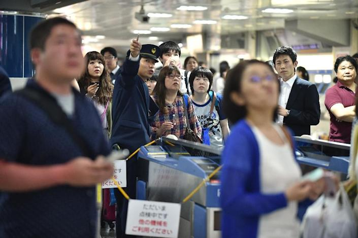 """Passengers wait for """"Shinkansen"""" bullet train operations to resume at a train station in Tokyo following a 7.8-magnitude earthquake shook buildings in the city on May 30, 2015 (AFP Photo/Kazuhiro Nogi)"""