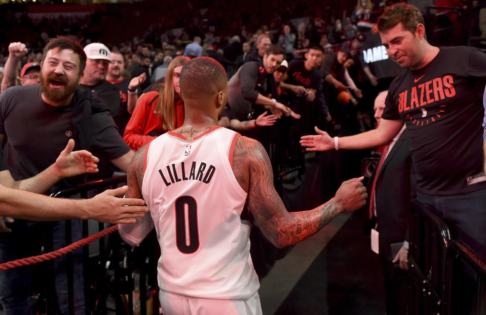 Fans greet Damian Lillard #0 of the Portland Trail Blazers as he walks off the court after the game at the Moda Center on April 14, 2019 in Portland, Oregon. The Blazers won 104-99.  NOTE TO USER: User expressly acknowledges and agrees that, by downloading and or using this photograph, User is consenting to the terms and conditions of the Getty Images License Agreement.  (Photo by Steve Dykes/Getty Images)