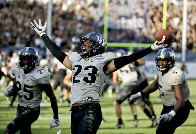"Central Florida defensive back <a class=""link rapid-noclick-resp"" href=""/ncaaf/players/244571/"" data-ylk=""slk:Tre Neal"">Tre Neal</a> (23) celebrates after intercepting a Memphis pass to end the American Athletic Conference championship NCAA college football game, Saturday, Dec. 2, 2017, in Orlando, Fla. Central Florida won in overtime 62-55. (AP Photo/John Raoux)"
