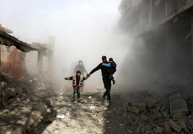 <p>Syrian civlians flee from reported regime air strikes in the rebel-held town of Jisreen, in the besieged Eastern Ghouta region on the outskirts of the capital Damascus, on Feb. 8, 2018. (Photo: Abdulmonan Eassa/AFP/Getty Images) </p>