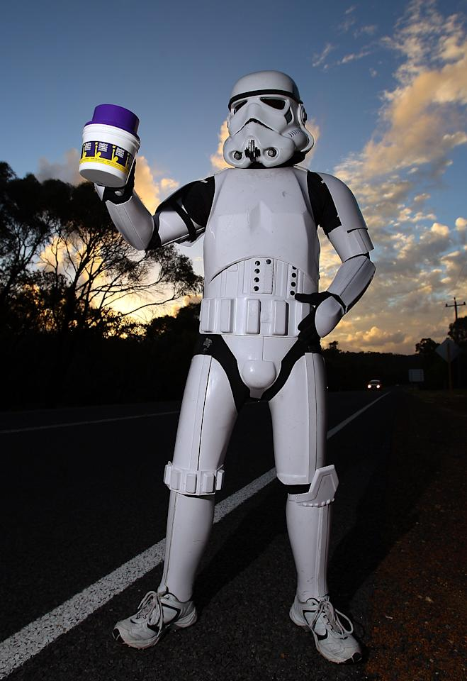 PERTH, AUSTRALIA - JULY 15:  Stormtrooper Paul French is pictured on day 5 of his over 4,000 kilometre journey from Perth to Sydney holding his collection tin on Old Mandurah Road on July 15, 2011 in Perth, Australia. French aims to walk 35-40 kilometres a day, 5 days a week, in full Stormtrooper costume until he reaches Sydney. French is walking to raise money for the Starlight Foundation - an organisation that aims to brighten the lives of ill and hostpitalised children in Australia.  (Photo by Paul Kane/Getty Images)