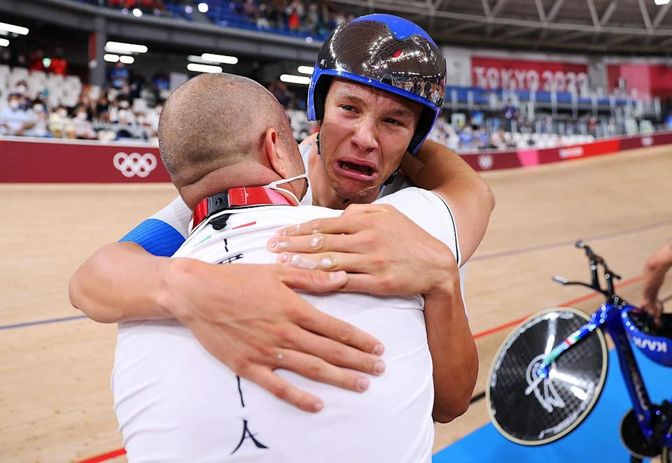 <p>Jonathan Milan of Team Italy is congratulated by his coach Marco Villa after winning the gold medal and setting a new World record during the Men's cycling team pursuit finals at Izu Velodrome on August 4.</p>