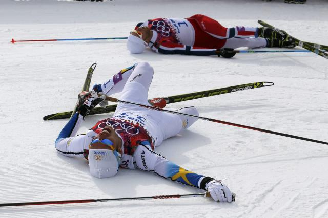 Second-placed Marcus Hellner (L) of Sweden and third-placed Martin Johnsrud Sundby of Norway react after crossing the finish line during the men's skiathlon event at the Sochi 2014 Winter Olympics in Rosa Khutor February 9, 2014. REUTERS/Stefan Wermuth (RUSSIA - Tags: SPORT OLYMPICS SPORT SKIING)