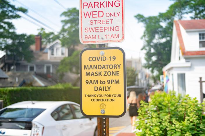 street sign attached to parking pole says 'covid-19 mandatory mask zone 9 am to 9 pm daily'